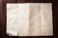 Vintage broken empty folded and crumpled paper on dark wooden table Stock Images