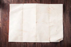 Vintage broken empty folded and crumpled paper on dark wooden table Stock Photos