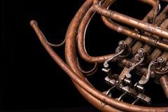 Vintage bronze pipes, valve, key mechanical elements french horn, black background. Good pattern, prompt music instrument. Vintage bronze pipes, valve, key royalty free stock photography