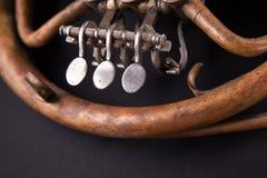 Vintage bronze pipes, valve, key mechanical elements french horn, black background. Good pattern, prompt music instrument. Vintage bronze pipes, valve, key royalty free stock image
