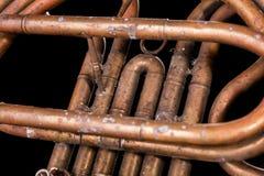 Vintage bronze pipes, valve, key mechanical elements french horn, black background. Good pattern, prompt music instrument. Vintage bronze pipes, valve, key stock photo