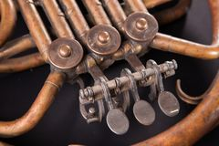 Vintage bronze pipes, valve, key mechanical elements french horn, black background. Good pattern, prompt music instrument. Vintage bronze pipes, valve, key stock photography