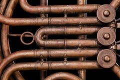 Vintage bronze pipes, valve, key mechanical elements french horn, black background. Good pattern, prompt music instrument. Vintage bronze pipes, valve, key stock image