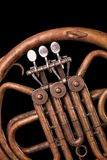 Vintage bronze pipes, valve, key mechanical elements french horn, black background. Good pattern, prompt music instrument. Vintage bronze pipes, valve, key stock images