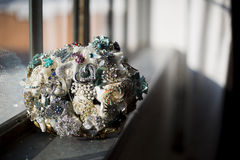 Vintage brooch jewelry wedding bouquet. Vintage wedding bouquet made from sparkling heirloom jewelry and brooches sitting on windowsill Stock Photo