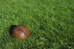 Vintage Brown Football Soccer Ball Green Grass Field. Vintage old brown football old-fashioned soccer ball sits in sunny green grass field stock image