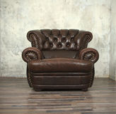Vintage brown leather chair in empty room Royalty Free Stock Image