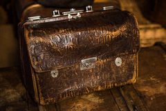 Vintage brown leather valise. With metal parts on a wooden table Royalty Free Stock Photo