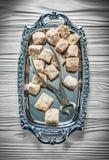 Vintage brown sugar pliers metallic tray on wooden board Royalty Free Stock Image
