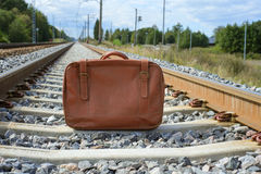 Vintage brown suitcase on the railway Stock Photo