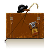 Vintage brown threadbare suitcase with walking stick, bowler hat Royalty Free Stock Photos