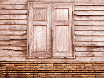 Vintage brown unique ancient wooden window and old crack brick wall retro style in rural for background Stock Image
