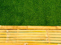 Vintage brown and yellow bamboo with fresh green grass background Royalty Free Stock Photo