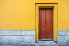 Vintage building with red wooden door and yellow concrete wall Stock Images