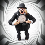 Vintage business man stuck with clock. Time crunch. Vintage business man holding clock while stuck in a tight time pressured schedule. Time crunch concept Stock Photo