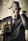 Vintage business man using retro telephone. Image of a old fashioned vintage business man standing in a office communicating to the exchange through a retro box