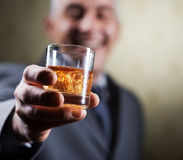 Vintage businessman holding a glass of whisky. Businessman holding a glass of whisky, close up Stock Photo
