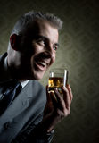 Vintage businessman holding a glass of whisky Stock Images