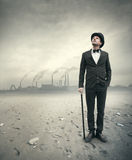 Vintage businessman in post atomic setting. Vintage businessman looking away with polluting factory and post atomic landscape on background Stock Photos