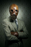 Vintage businessman wearing gas mask. Vintage businessman wearing a gas mask with retro wallpaper on background Royalty Free Stock Image