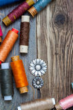 Vintage buttons and oldreels of varicolored thread on the text Royalty Free Stock Photography
