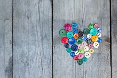 Vintage buttons in the shape of a heart on a wooden background Stock Photo