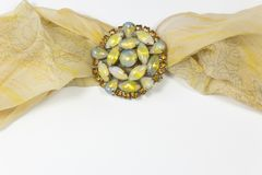 Vintage cabochon brooch with amber rhinestones and a sheer yellow scarf. On white, horizontal aspect Stock Photos