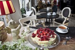 Vintage cafe, on the old steel cake with berries, a cup of tea, a milk jug and a bear with wings.  royalty free stock photos