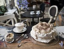 Vintage cafe, on the old steel meringue cake with berries, dessert, a cup of tea stock photography