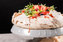 Pavlova meringue cake dessert made with strawberries, kiwi, blueberries and mint royalty free stock photography