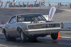 Vintage camaro drag car. Front side view of vintage camaro drag car making a wheelie at the starting line on the track during the grand national show, august 27 Stock Image