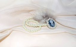 Vintage cameo with fur and pearls. Vintage Vintage cameo on white cloth with fur and pearls royalty free stock photos