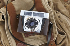 Vintage camera with backpack on the ground. Travel Royalty Free Stock Photography