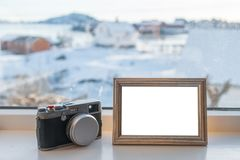 Vintage Camera with blank picture frame on window sill. In winter season royalty free stock photos