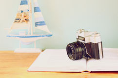Vintage camera, book and decorations over wooden shelf. Royalty Free Stock Image