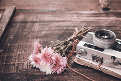 Vintage camera with bouquet of flowers on old wood background stock photo