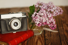 Vintage camera and Bouquet of lilac spring flowers Royalty Free Stock Photo
