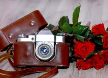 vintage camera with a bouquet of roses stock photos
