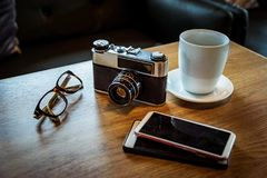 Vintage camera with coffee cup, glasses and smartphone on the ta Royalty Free Stock Images