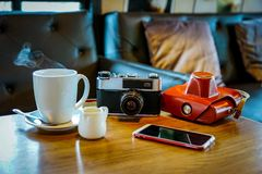 Vintage camera with coffee cup, glasses and smartphone on the ta Stock Photo