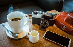 Vintage camera with coffee cup, glasses and smartphone on the ta Royalty Free Stock Photography