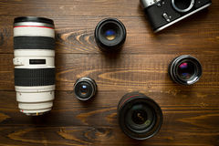 Vintage camera and different lenses lying on wooden background Royalty Free Stock Photo
