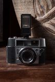 Vintage camera with flash. On wooden surface Stock Photo