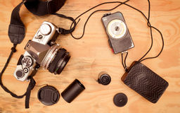 Vintage camera. Flat lay - vintage film camera and accesories (lightmeter, film stock, shoulder strap, film canister) on wooden desk royalty free stock photos