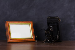 Vintage camera and frame against blackboard background Stock Photography