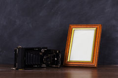 Vintage camera and frame against blackboard background Royalty Free Stock Photo