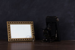 Vintage camera and frame against blackboard background Stock Photo