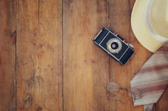 Vintage camera, glasses and fedora hat on wooden table Royalty Free Stock Photos