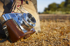 Vintage camera with hiking boots on the ground. Travel Stock Photo