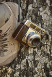Vintage camera with hiking boots and tree trunk. Travel Stock Images
